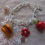 Bracelet fraise, macaron, fleur et cage spirales, sur grosse chaine argentée.