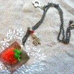 Collier réversible fraise dans résine moulée, sur chaine argentée.
