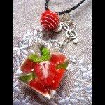 Collier réversible fraise dans résine moulée, sur lien cuir tréssé.