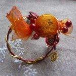 Bracelet macaron orange sur fils alu dorés et rouges.