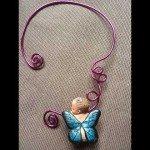 Collier bébé papillon bleu turquoise sur cable rose.