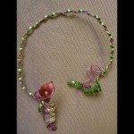 Collier arum pailletté, dans fiole et résine coulée, fil alu rose et vert anis.