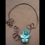 Collier bébé papillon habillé turquoise, sur cable brun.